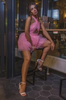 Giovane donna alla moda carina in bellissimo vestito lucido su sfondo scuro ristorante interno. bella donna in posa per attività pubblicitarie fotografiche.
