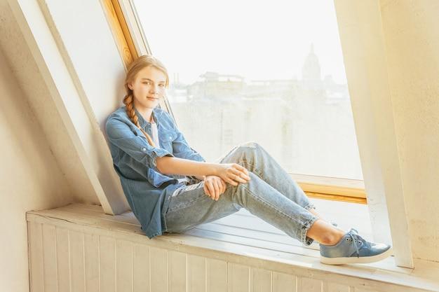 Giovane adolescente carina in jeans, giacca di jeans e maglietta bianca seduta sul davanzale della finestra in un soggiorno luminoso e luminoso a casa al chiuso e pensando. concetto di jomo distanza sociale.