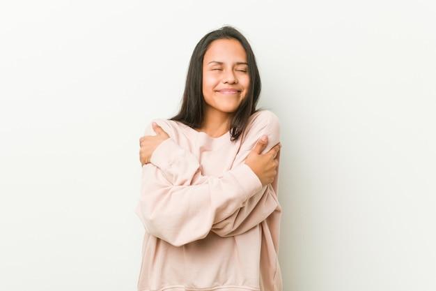 Abbracci di donna giovane adolescente carino, sorridente spensierato e felice.