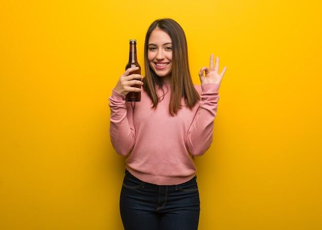 Giovane donna carina che tiene una birra allegra e sicura che fa gesto giusto