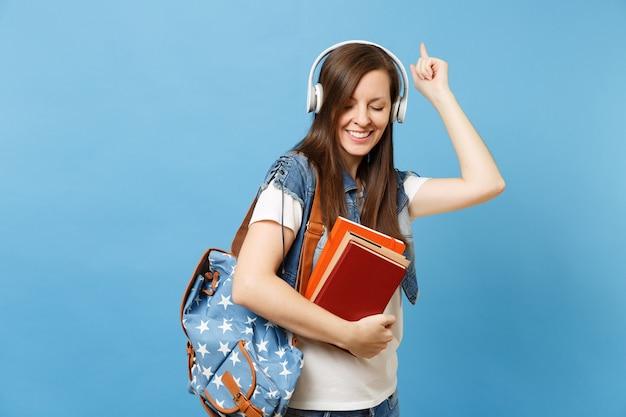 La giovane studentessa sveglia in vestiti del denim con le cuffie dello zaino ascolta la musica della tenuta del libro di scuola che indica la danza del dito indice isolata su fondo blu. istruzione al college universitario di scuola superiore.