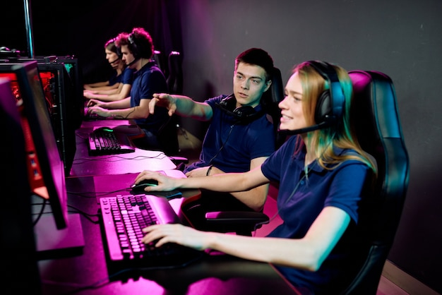 Giovane giocatore di cyber sport che dà consigli alla ragazza in cuffia mentre si prepara per la competizione di e-sport