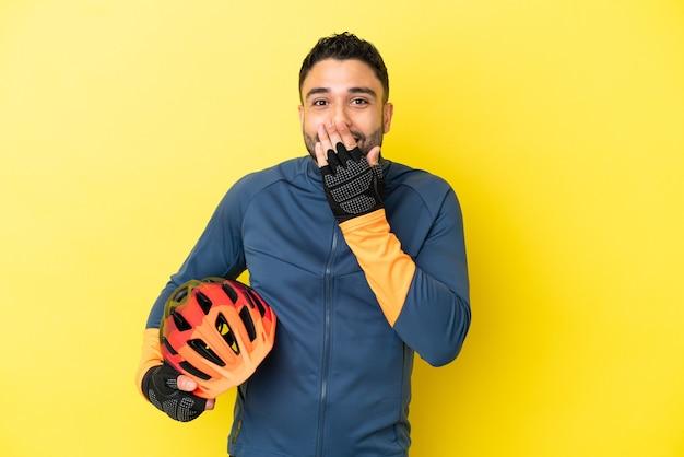 Giovane ciclista uomo arabo isolato su sfondo giallo felice e sorridente che copre la bocca con la mano