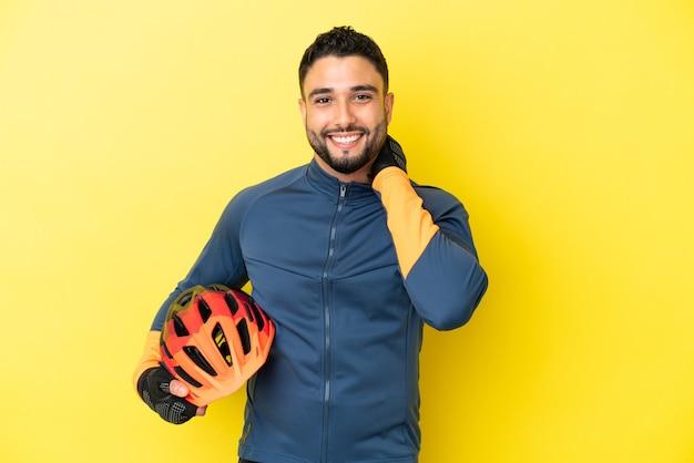 Giovane ciclista uomo arabo isolato su sfondo giallo che ride