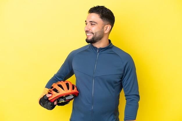 Uomo arabo del giovane ciclista isolato su fondo giallo che guarda side