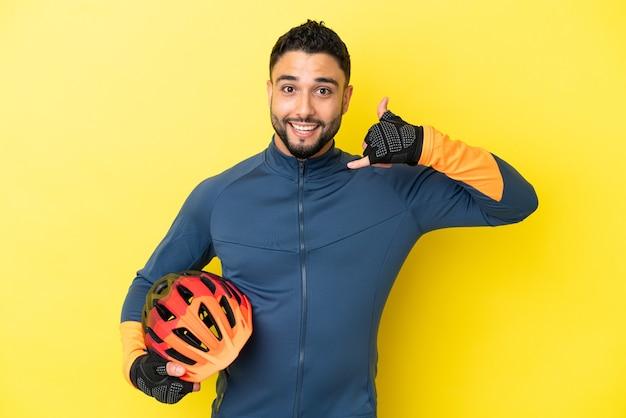Uomo arabo del giovane ciclista isolato su fondo giallo che fa gesto del telefono. richiamami segno