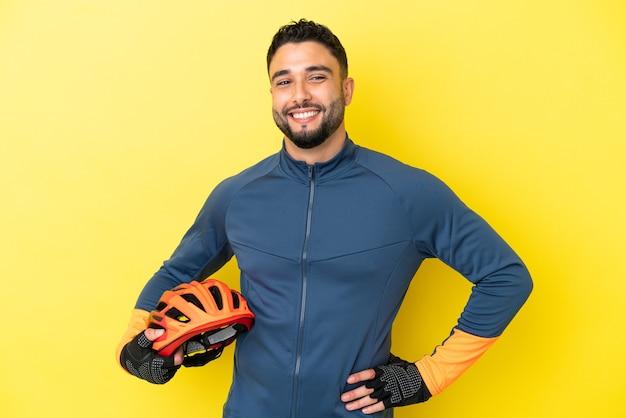 Giovane ciclista uomo arabo isolato su sfondo giallo in posa con le braccia all'anca e sorridente