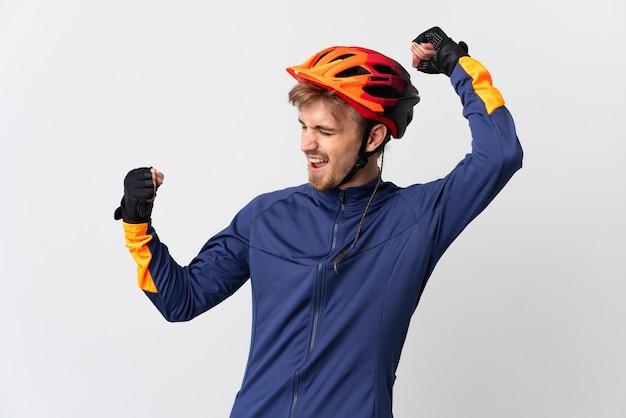 Uomo biondo del giovane ciclista isolato che celebra una vittoria