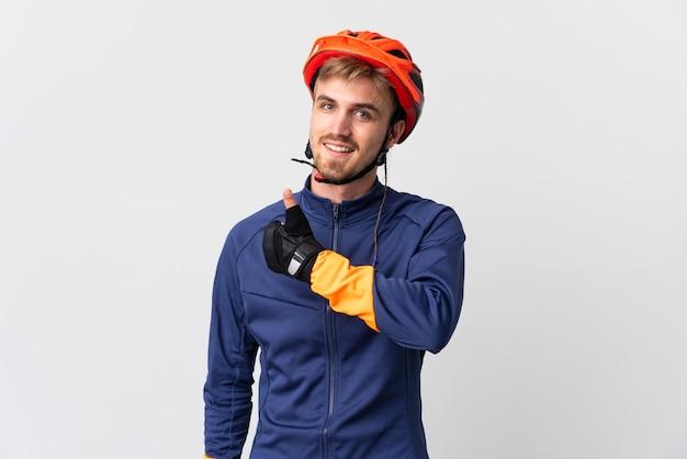 Uomo biondo del giovane ciclista isolato che dà i pollici aumenta il gesto