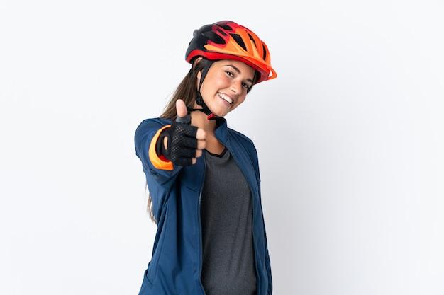 Ragazza brasiliana giovane ciclista isolata sul muro bianco con i pollici in su perché è successo qualcosa di buono