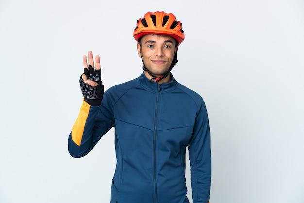 Uomo brasiliano giovane ciclista isolato sul muro bianco felice e contando tre con le dita