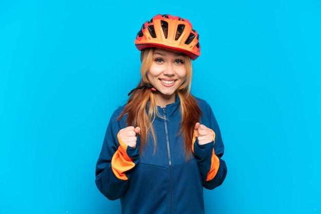 Ragazza giovane ciclista isolata su priorità bassa blu che celebra una vittoria nella posizione del vincitore