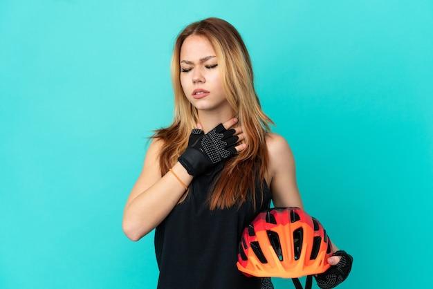 Ragazza giovane ciclista su sfondo blu isolato che tossisce molto