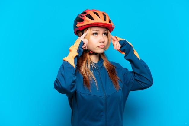 Ragazza giovane ciclista isolata su sfondo blu che ha dubbi e pensa