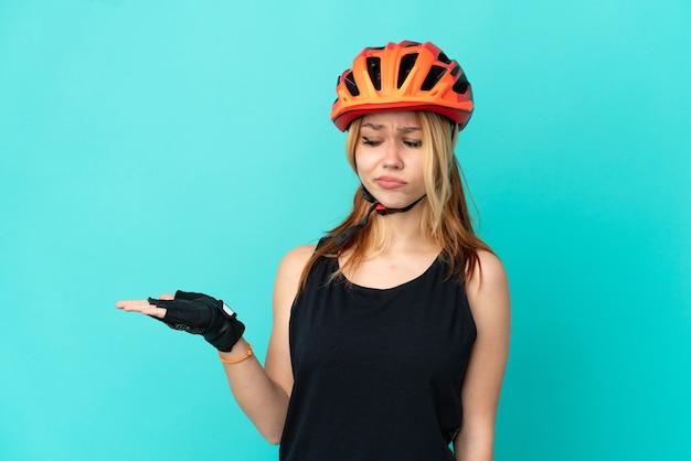 Ragazza giovane ciclista su sfondo blu isolato tenendo copyspace con dubbi doubt