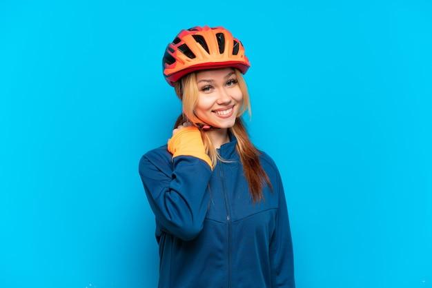 Ragazza giovane ciclista isolata su sfondo blu ridendo