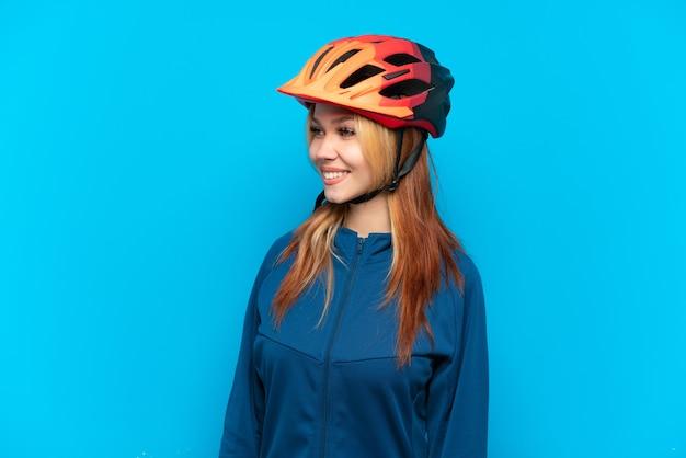 Ragazza giovane ciclista isolata su sfondo blu guardando il lato