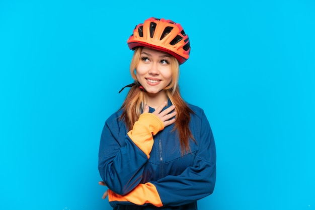 Ragazza giovane ciclista isolata su sfondo blu guardando in alto mentre sorride