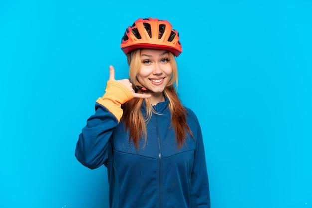 Ragazza giovane ciclista isolata su sfondo blu che fa gesto di telefono. richiamami segno