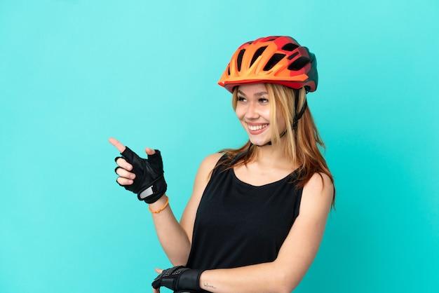 Ragazza giovane ciclista su sfondo blu isolato che punta il dito di lato e presenta un prodotto
