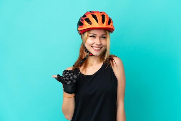 Ragazza giovane ciclista su sfondo blu isolato che punta al lato per presentare un prodotto
