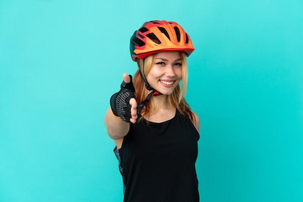 Ragazza giovane ciclista su sfondo blu isolato che stringe la mano per aver chiuso un buon affare