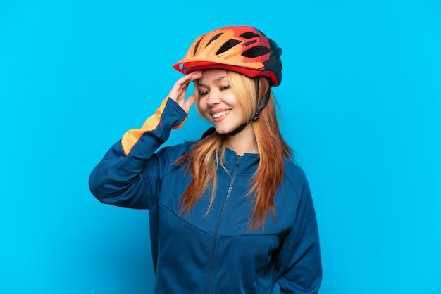 Ragazza giovane ciclista isolata su sfondo blu sorridente molto
