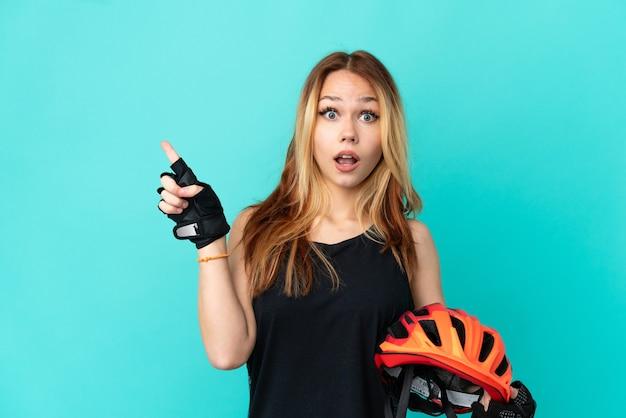 La giovane ragazza del ciclista sopra fondo blu isolato ha sorpreso e che indica il dito al lato