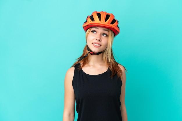 Ragazza giovane ciclista su sfondo blu isolato pensando a un'idea mentre guarda in alto