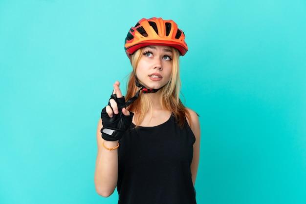 Ragazza giovane ciclista su sfondo blu isolato con le dita incrociate e augurando il meglio