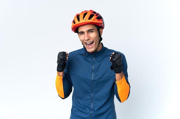 Uomo giovane ciclista isolato su sfondo che celebra una vittoria nella posizione del vincitore