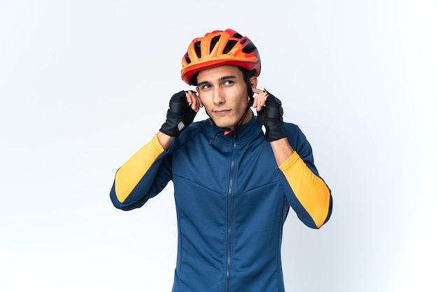 Uomo giovane ciclista isolato su sfondo frustrato e che copre le orecchie