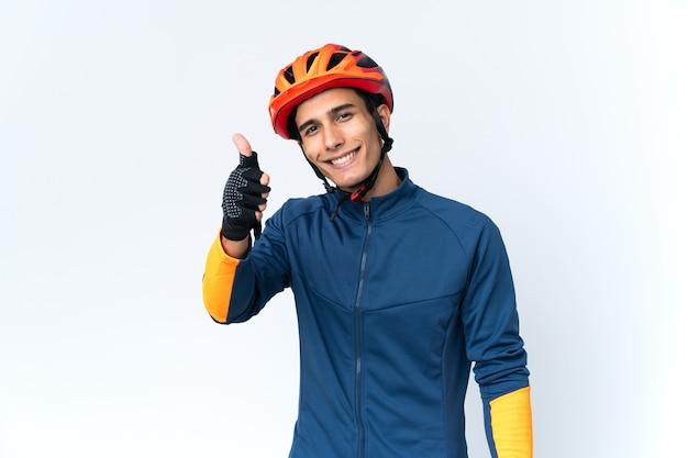 Uomo giovane ciclista isolato su sfondo con i pollici in su perché è successo qualcosa di buono