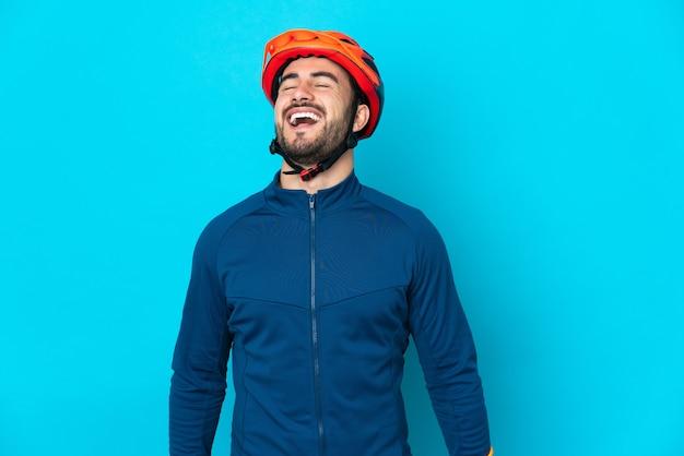 Uomo giovane ciclista isolato su sfondo blu ridendo