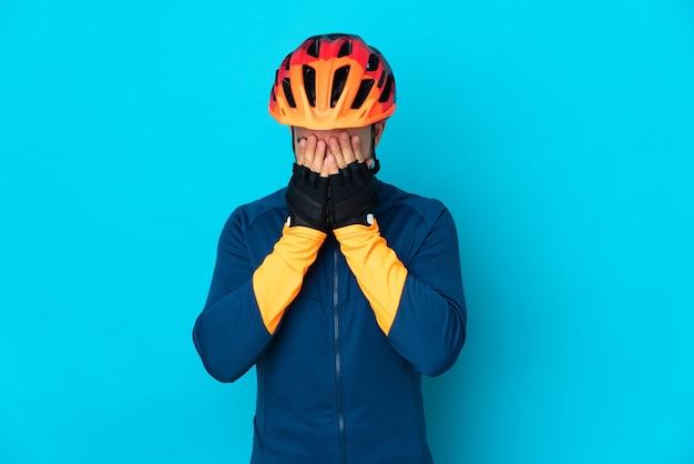 Uomo giovane ciclista isolato su sfondo blu con espressione stanca e malata