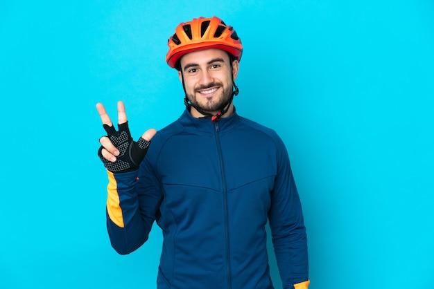 Uomo giovane ciclista isolato sulla parete blu felice e contando tre con le dita