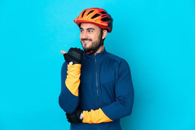 Uomo giovane ciclista isolato sulla parete blu che punta di lato per presentare un prodotto