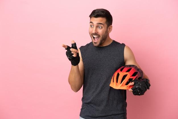 Giovane ciclista isolato su sfondo rosa che punta il dito di lato e presenta un prodotto