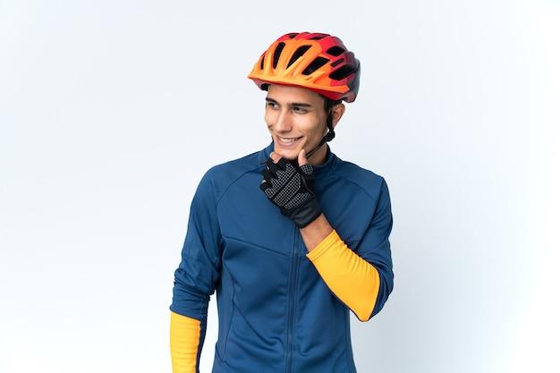 Uomo giovane ciclista isolato sulla parete che guarda al lato e sorridente