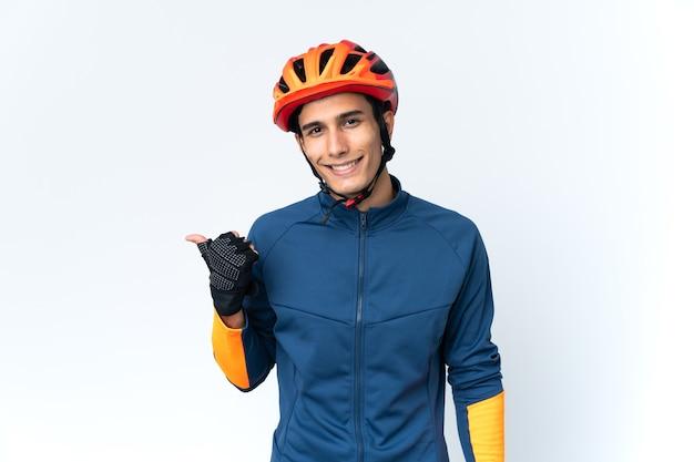 Uomo giovane ciclista isolato sulla parete che punta di lato per presentare un prodotto