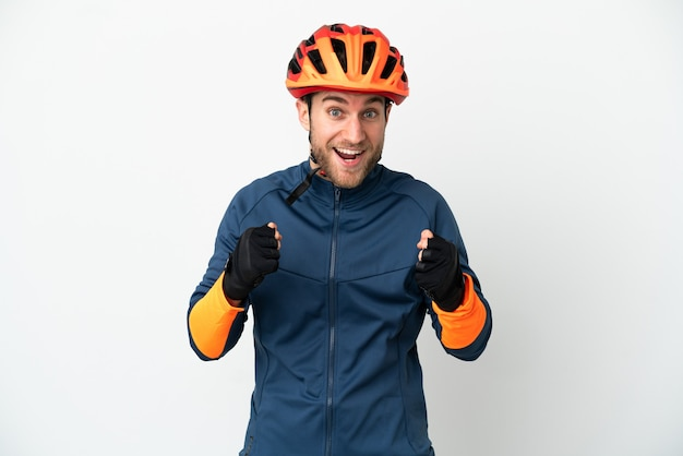 Uomo giovane ciclista isolato su sfondo bianco che celebra una vittoria nella posizione del vincitore