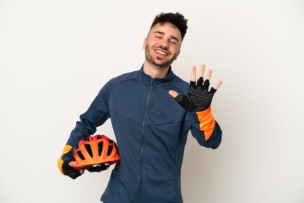 Uomo giovane ciclista isolato su sfondo bianco contando cinque con le dita