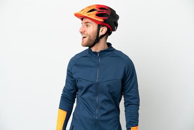 Uomo giovane ciclista isolato su sfondo bianco che ride in posizione laterale