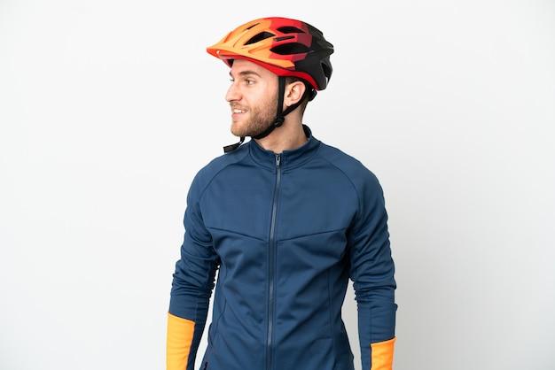 Uomo giovane ciclista isolato su sfondo bianco cercando di lato