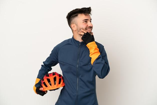 Uomo giovane ciclista isolato su sfondo bianco guardando in alto sorridendo
