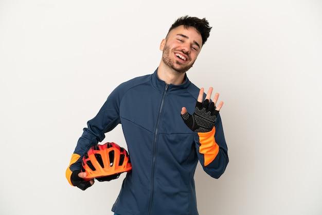 Uomo giovane ciclista isolato su sfondo bianco salutando con la mano con espressione felice