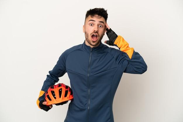 Uomo giovane ciclista isolato su sfondo bianco con espressione di sorpresa