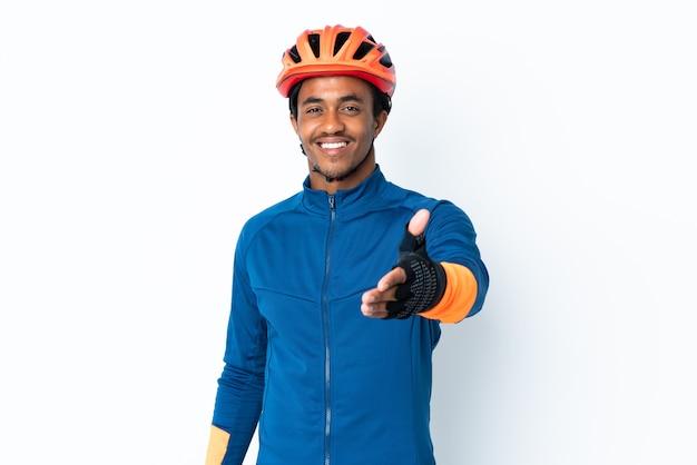 Giovane ciclista uomo con trecce su sfondo isolato si stringono la mano per chiudere un buon affare