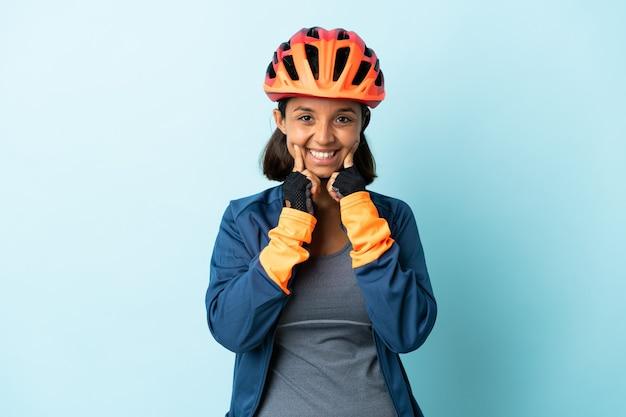 Giovane donna ciclista sull'azzurro che sorride con un'espressione felice e piacevole