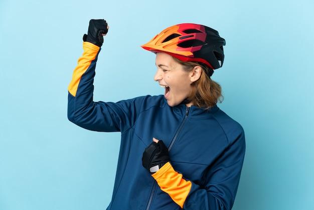 Donna giovane ciclista isolata su sfondo blu che celebra una vittoria